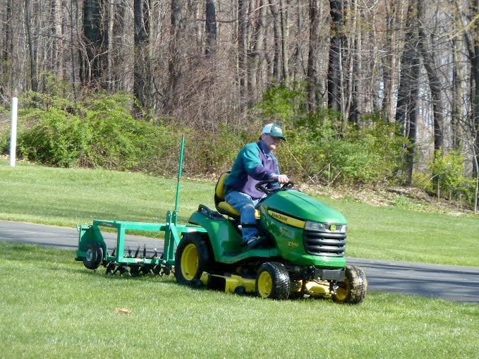 technician using equipment to perform aeration and overseeding