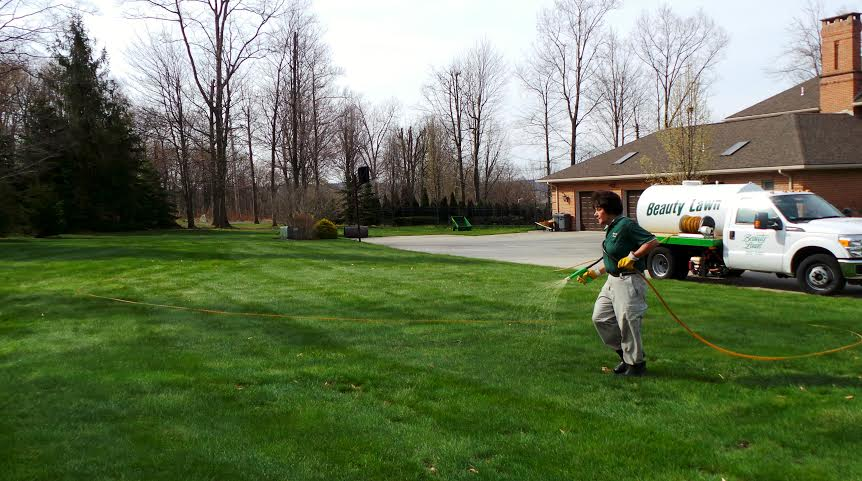 technician performing lawn spraying service