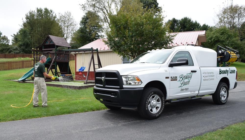 Beauty Lawn truck and technician spraying yard along swing set