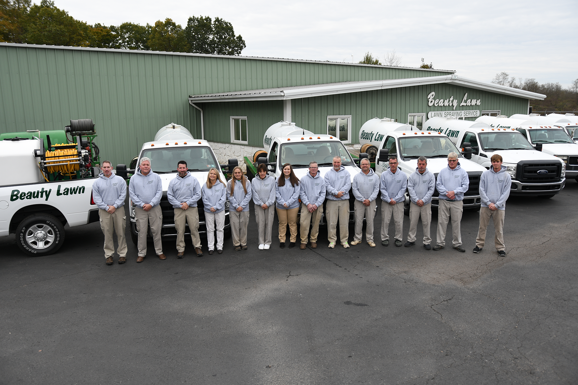 Beauty Lawn staff standing in front of trucks and building